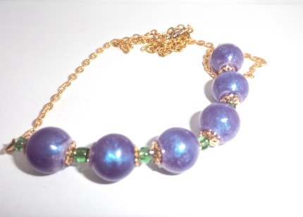 Purple resin bead necklace $20.00: Purple pearlized round resin & green beads, with metal flower fixings & gold coloured chain. Length 60cm.