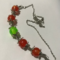 Orange & Green round resin bead necklace $20.00: 4 orange, 1 green 1cm resin beads, with steel finings & chain. Length 52cm.